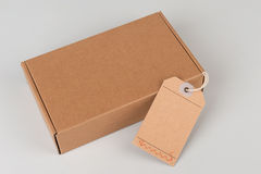 Parcel. cardboard box with blank tag Stock Image