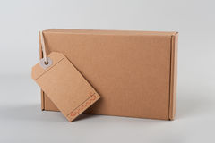 Parcel. cardboard box with blank tag Royalty Free Stock Photography