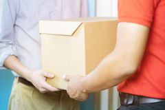 Parcel delivery man of a package through a service. and close up hand customer accepting a delivery royalty free stock images