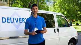 Parcel delivery worker filling report and smiling, part-time job, occupation. Stock photo stock photos