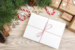 Parcel in Envelope with Fir-tree Branches and christmas decoration on a Wooden Background Stock Photography