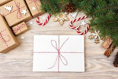 Parcel in Envelope with Fir-tree Branches and christmas decoration on a Wooden Background Stock Photos