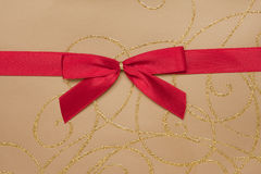 Parcel with gold paper and red ribbon Stock Photography