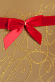 Parcel with gold paper and red ribbon Royalty Free Stock Image