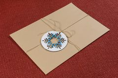 Parcel, letter, packed in a vintage envelope with symbolic snowflake. New Year and Christmas holidays. Royalty Free Stock Photos