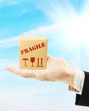 Parcel lies on a male hand against blue sky Royalty Free Stock Image
