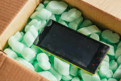 Parcel of online shop, phone in a cardboard box on green styrofoam Royalty Free Stock Photos