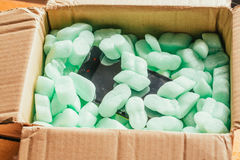 Parcel of online shop, phone in a cardboard box on green styrofoam Stock Photos