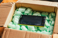 Parcel of online shop, phone in a cardboard box on green styrofoam Royalty Free Stock Images