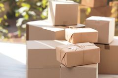 Parcel with tag and blurred stacked boxes on background. Indoors stock images