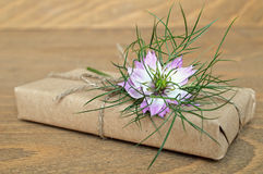 Parcel wrapped in brown paper and nigella flower. Parcel wrapped in brown paper and purple nigella flower royalty free stock photography