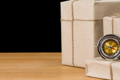 Parcel wrapped and compass on black Royalty Free Stock Photography