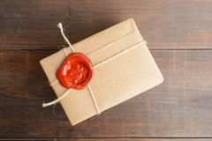 Parcel wrapped in craft paper with rope and red sealing wax over. Brown wooden table, overhead view stock photos