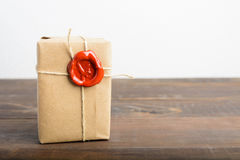 Parcel wrapped in craft paper with rope and red sealing wax over. The wooden table with white background royalty free stock photo