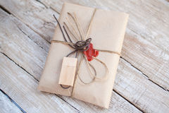 The parcel wrapped in Kraft on a wooden background. Royalty Free Stock Images