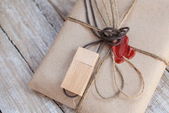 The parcel wrapped in Kraft on a wooden background. Royalty Free Stock Photos