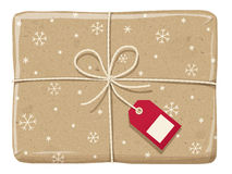 Parcel wrapped up with snowflake paper, tied up with twine. Parcel wrapped up with a snowflake paper, tied up with twine with red label royalty free stock photo