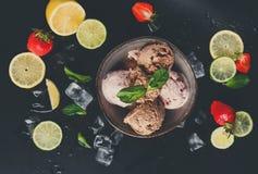 Parcela de colheres do gelado com fruto no preto Foto de Stock