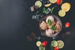 Parcela de colheres do gelado com fruto no preto Fotografia de Stock Royalty Free
