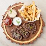 Parcela de mignon de faixa da carne do BBQ com molhos e as batatas fritadas Imagens de Stock Royalty Free