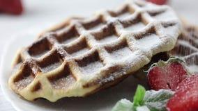 Parcela de waffles belgas com as morangos frescas na placa A mão do ` s do cozinheiro chefe que polvilha o pó do açúcar da sobrem filme