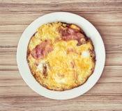 Parcela grande de presunto saboroso e de ovos na placa branca Imagem de Stock