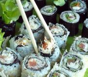 Parcelas de rolos de sushi com salada e ingredientes Fotografia de Stock