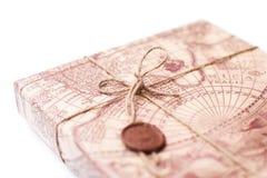 Parcele o pacote envolvido com corda amarrada marrom do papel de embalagem em um whi Imagens de Stock Royalty Free