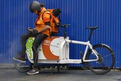 Parcele o trabalhador da entrega em sua bicicleta da carga que consulta seu smartphone fotografia de stock royalty free