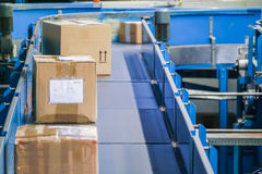 Parcels on conveyors with blurred industrial background Royalty Free Stock Photos