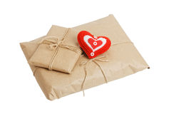 Parcels with kraft paper and red heart isolated on white. Two parcels with kraft paper tied with twine and small handmade red heart isolated on white background Royalty Free Stock Photography