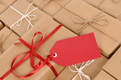 Red gift tag with background of several brown paper packages, copy space Royalty Free Stock Photos