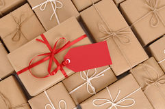 Red gift tag with rows of brown paper packages in background, copy space Stock Image
