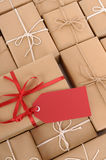 Red gift tag with background of brown paper packages in a row, copy space, vertical Royalty Free Stock Photography