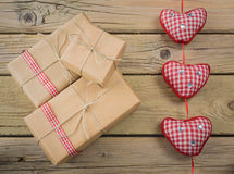 Parcels wrapped in brown paper and string with red check ribbon Royalty Free Stock Images