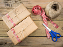 Parcels wrapped in brown paper and string with ribbon and scisso Stock Image