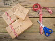 Parcels wrapped in brown paper and string with ribbon and scisso Royalty Free Stock Photography