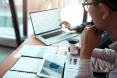 A parceria do negócio que aponta ao gráfico dos balanços financeiros da empresa relata e os lucros ganharam durante no computador fotos de stock