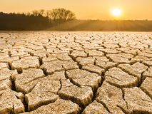Parched knäckte jord i landskap på soluppgång royaltyfri fotografi