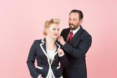 Parchefer i dräkter Framstickandedressing på flickahalsperls Den gjorda mannen framlägger till affärskvinnan Man och kvinna i blå royaltyfria foton