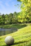 Parcheggi con il bacino sul tramonto e sulla palla da golf della statua Fotografia Stock Libera da Diritti