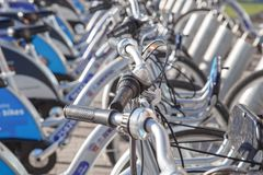 Parcheggiando per le biciclette Bici da affittare timone Trasporto ecologico per grandi città Freno delle assicelle e di un casco Fotografia Stock