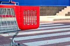 Parcheggiando vicino al supermercato con il carrello rosso di acquisto immagini stock libere da diritti
