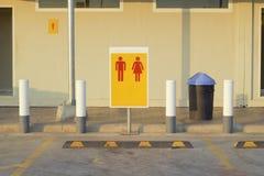 Parcheggio davanti al bagno nella stazione di servizio, segni, donne, fondo giallo rosso degli uomini Icone della donna e dell'uo immagine stock