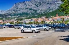 Parcheggio delle automobili sull'argine della città sui precedenti delle montagne fotografia stock libera da diritti