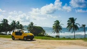 Parcheggio turistico dell'automobile davanti ad una spiaggia sola in Barbados Immagini Stock