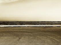 Parcheggio vuoto con la guardavia, tonalità granulare di seppia fotografia stock libera da diritti