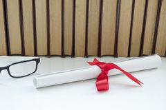 A parchment diploma scroll, rolled up with red ribbon beside a stack of books on white background. royalty free stock image