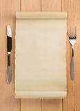 Parchment and fork with knife on wood. En background stock image