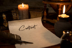 Parchment paper with a quill and ink, candles and medieval decor stock image